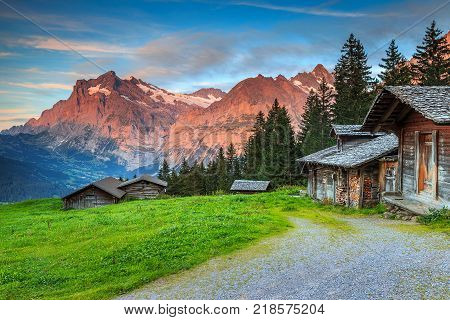 Beautiful alpine landscape, old Swiss traditional wooden hut and magical sunset with Wetterhorn peak in background, Grindelwald, Bernese Oberland, Switzerland, Europe