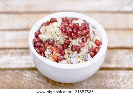 Quinoa salad with Pomegranate seeds, radicchio, cucumber and olives on light brown background
