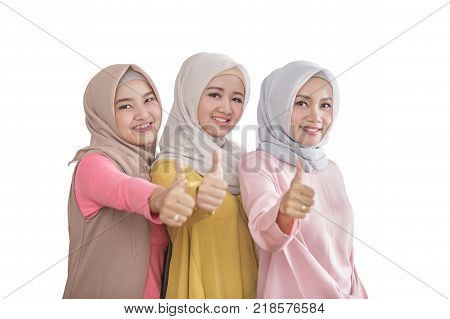 portrait of three beautiful siblings smiling and giving thumbs up isolated on white background