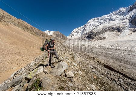 A white tanned mountaineering woman of about 40 years old with a backpack on her shoulders posing against the beautiful view of the Bezengi glacier in the Central Caucasus Russia.