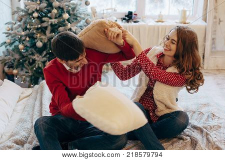 Happy loving caucasian couple is getting crazy on the Christmas eve near the New Year tree, they are sitting on the bed, laughing a lot, fighting with pillows