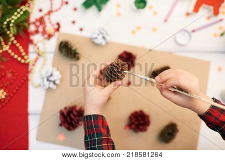 Close-up shot of unrecognizable little girl standing at wooden desk and covering pinecone with gouache while making decorations for Christmas