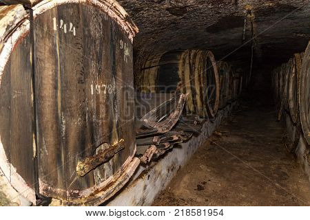 broken old oak barrels, An old wine cellar with oak barrels, barrels for wine in old cellars