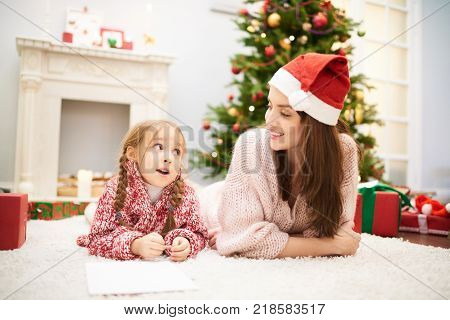 Lovely family portrait: adorable little girl wearing knitted sweater lying on cozy carpet by fireplace and chatting with her mom, interior of living room with decorated Christmas tree on background