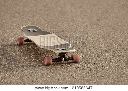 Outdoor picture of shabby skateboard with orange wheels resting isolated on textured paved concrete road left by its careless teen owner. Skateboarding youth subculture and urban lifestyle