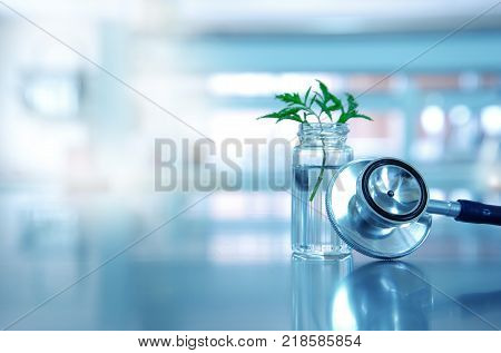 stethoscope for health medical doctor diagnosis with vial glass and green leave plant in blue light background