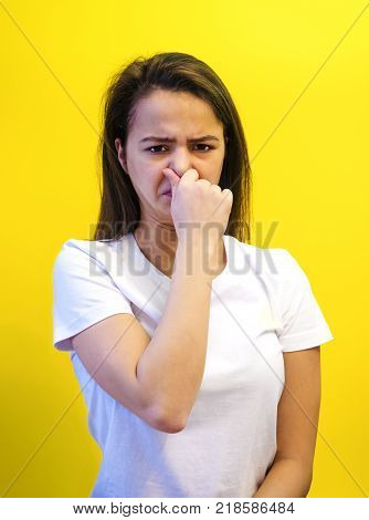 A young European woman holding her nose because of a bad smell on a yellow background