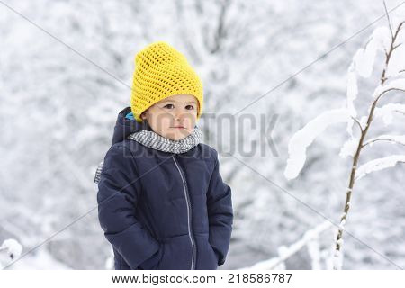 Winter children clothes. Warm jacket and hat for toddler. Boy warms hands in pockets without winter gloves. Beautiful child on winter nature background snow. Cold and frost fashion cute yellow hat