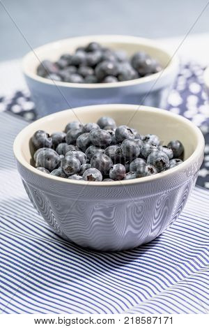 Blueberries in small gray bowl on light blue background