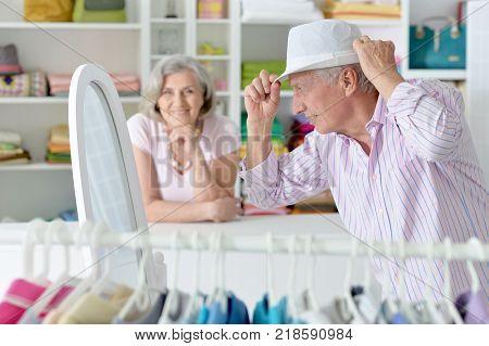 Senior couple choosing hat in a shop