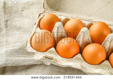 Raw brown chicken eggs in a cardboard tray with cells on sacking on a white wooden table. Ingredients for cooking