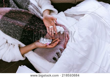 the girl fell ill with angina because of the cold winter weather, lies in bed, holds a pill in her hand