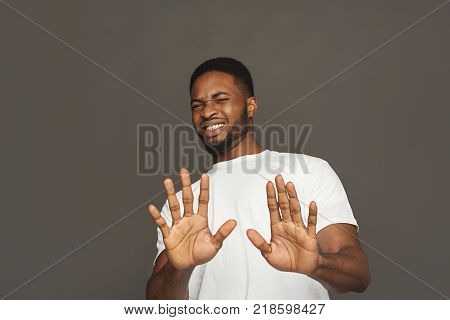 man expressing disgust on face, grimacing on white studio background. Negative emotions