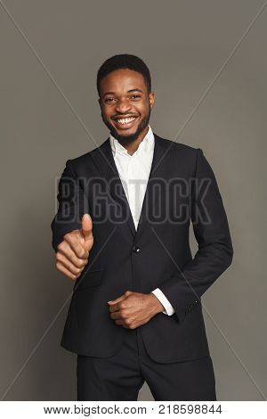 Happy smiling  man showing thumb up gesture, man portrait in formal wear, standing on grey background, studio shot