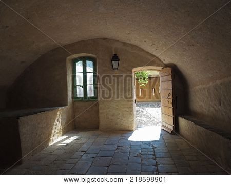 medieval house with barrel vault open door lantern green window and yard view yellow stone walls and cobblestone paving in corte castle
