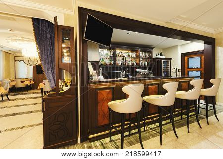 Hotel lounge bar with bottle shelves and seats. Barroom in restaurant, ready for work, copy space. Cafe background