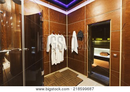 Luxury dressing room in sauna with new white bathrobes and shower, and door to steam room. Spa procedures and wellness concept, copu