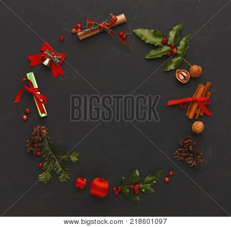 Christmas decoration handmade frame background, top view with copy space on black table. Creative diy craft hobby, xmas wreath with natural elements