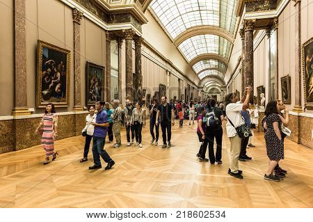 Paris France - July 01 2017: Tourists visit art gallery in the Louvre Museum. The Louvre Museum is one of the largest and most visited museums worldwide.