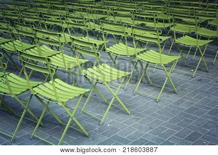 Empty green chairs in the park. Open-air theater seating after event. Seats with no people.