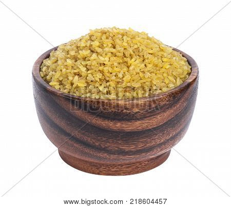 Dry bulgur wheat in wooden bowl isolated on white background. One of the collection