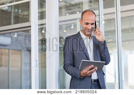 Smiling mature man looking at digital tablet while talking over phone. Mature businessman in a happy conversation over cellphone. Successful senior business man in formal talking over phone.