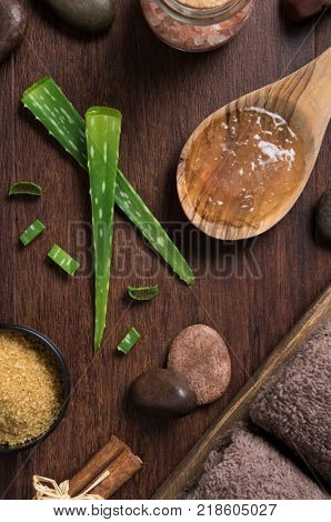 Stem of aloe vera plant on wooden background with himalayan salt and stones. Top view of aloevera gel on wooden spoon with beauty spa setting on table. High angle view of beauty treatment at spa.