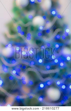 Decorated Christmas tree with blue lights. Unfocused image