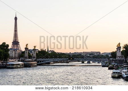 Eiffel Tower and Pont Alexandre III Bridge over river Seine decorated with ornate art nouveau lamps and sculptures at sunset in the summer. Paris France