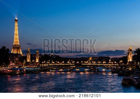 Paris France - July 02 2017: Beautiful night illumination of Eiffel Tower and Pont Alexandre III Bridge over river Seine decorated with ornate art nouveau lamps and sculptures in the summer.