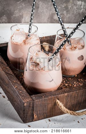 Summer refreshment drinks. Chilled iced chocolate cocoa. With scoop of chocolate ice cream chocolate powder and ice. In glasses with tubes for drinking. White concrete table wooden tray. Copy space