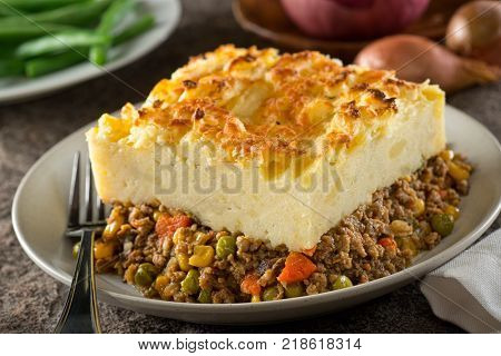 A serving of delicious homemade shepherd's pie with ground meat mashed potato carrots peas corn and cheddar cheese crust.