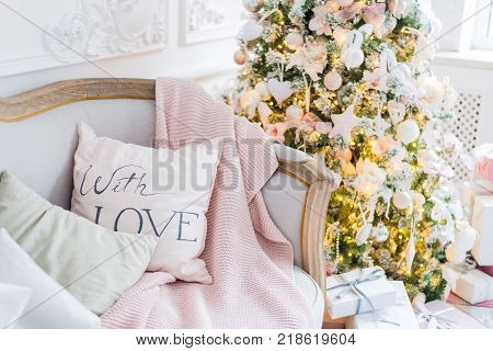 Christmas or new year decoration at Living room interior and holiday home decor concept. Calm image of blanket on a vintage sofa with tree, lifghts, gifts. Selective focus.