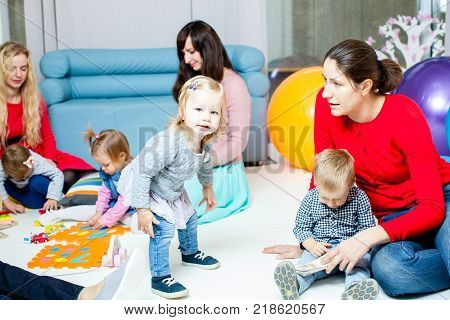 Mothers with their children play in the nursery, 1-2 years old toddlers indoor