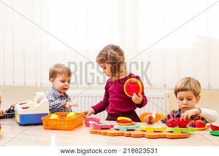 Children playing with children's housewares and artificial fruit in kindergarten