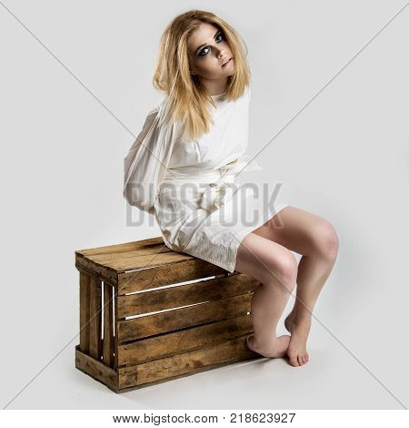 Portrait of a beautiful young crazy woman in straitjacket