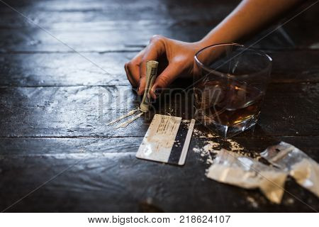 Cocaine and alcohol drink on dark background. Detrimental lifestyle. Bad habits. Alcohol and drug addiction. Important problem of modern society