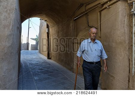 Yazd Iran - April 21 2017: An elderly Iranian man leaning on a cane passes under the clay vault of the gateway.