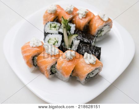 Philadelphia sushi rolls on a plate on white background. Asian cuisine and traditional Japanese food concept