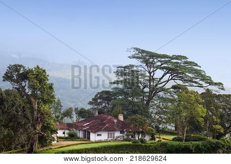Traditional house over tea plantations in Munnar, Kerala, South India. It is situated at around 1,600 meters above sea level in the Western Ghats range of mountains.
