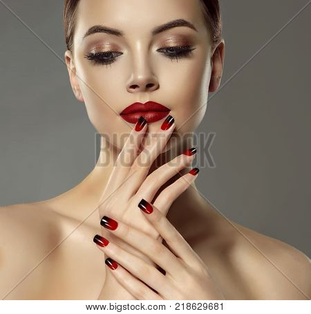 Beautiful model girl with red and black  french manicure on nails . Fashion luxury makeup . Dark red lips and shiny eye shadow pigment . Beauty  and cosmetics .