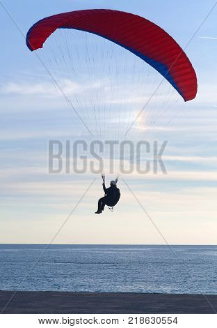 An unidentified paraglider flying at sunset over Blue lagoon in Oludeniz Turkey