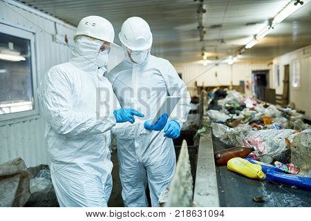 Portrait of two workers  wearing biohazard suits  using digital tablet  standing by conveyor belt at waste processing plant , copy space