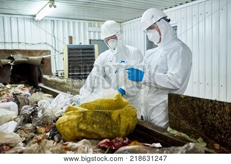 Portrait of two workers wearing biohazard suits sorting recyclable plastic and cardboard on conveyor belt at waste processing plant