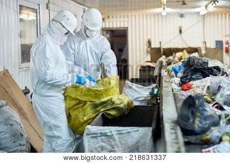 Side view  portrait of two workers wearing biohazard suits sorting recyclable plastic and cardboard on conveyor belt at waste processing plant