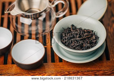 Set for Chinese tea ceremony, da hong pao oolong tea in gaiwan or tea-cup on a wooden table