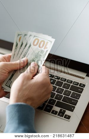 Online casino gambling. Man holding money and placing virtual bets using laptop. Luck success and winning concept