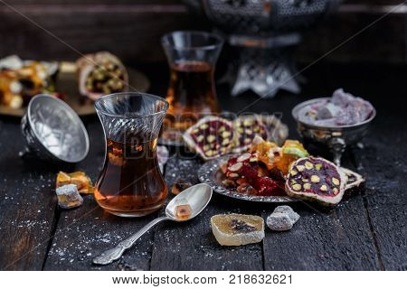 Turkish tea with authentic glass cups. Two cups of turkish tea and sweets on dark wood background.