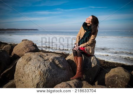 Young beautiful woman in elegant clothes with scarf sits on the coastline in winter season and closed her eyes. 1 person