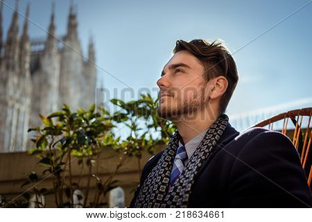 Young elegant man sitting on the chair in cafe-terrace in beautiful winter day in Milan. 1 person